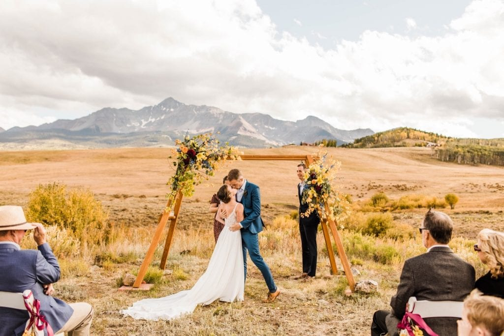 first kiss during a mountainous Telluride wedding ceremony at a horse ranch on Wilson Mesa