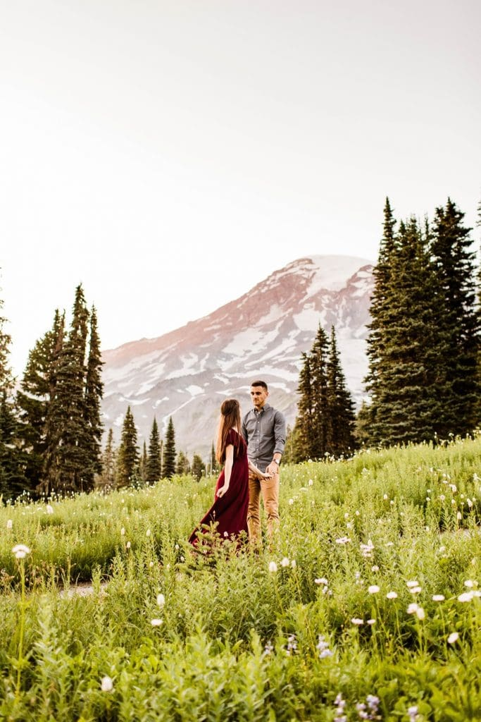 couple dancing together in an alpine wildflower meadow during their engagement photos in Seattle WA