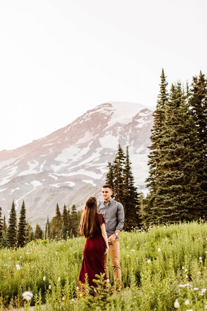 couple dancing together in an alpine meadow during their engagement photos in Seattle WA