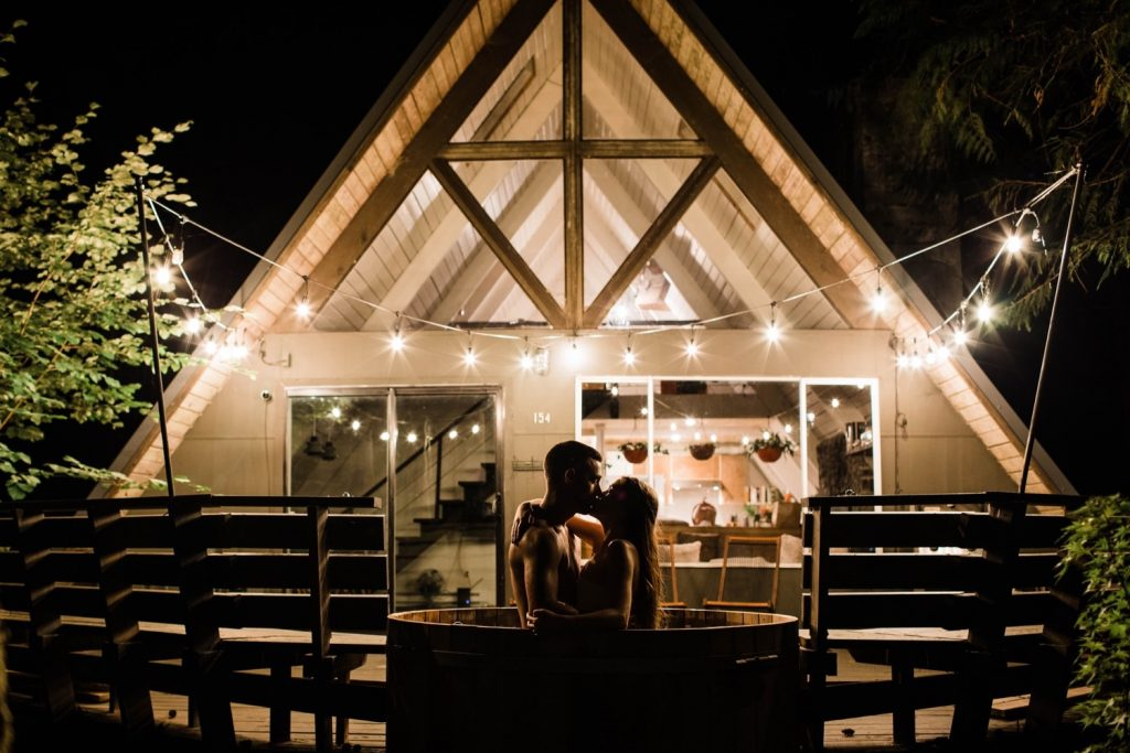 engagement photos in Seattle WA of a couple in their a-frame cabin hot tub at night