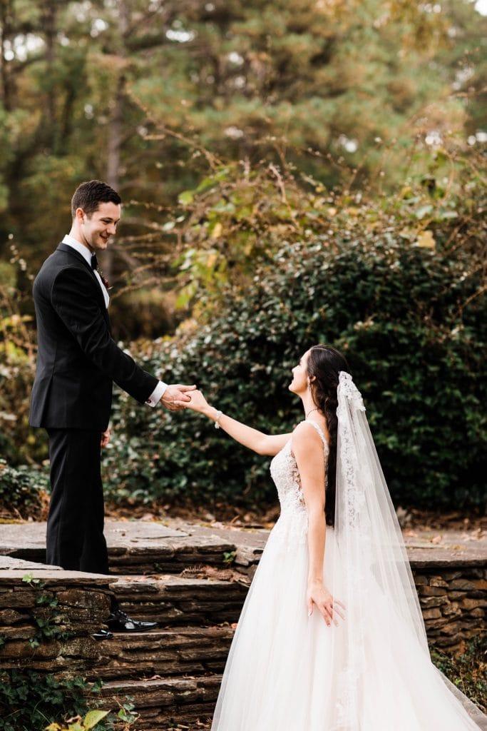 groom holding brides hand in Dunaway Gardens