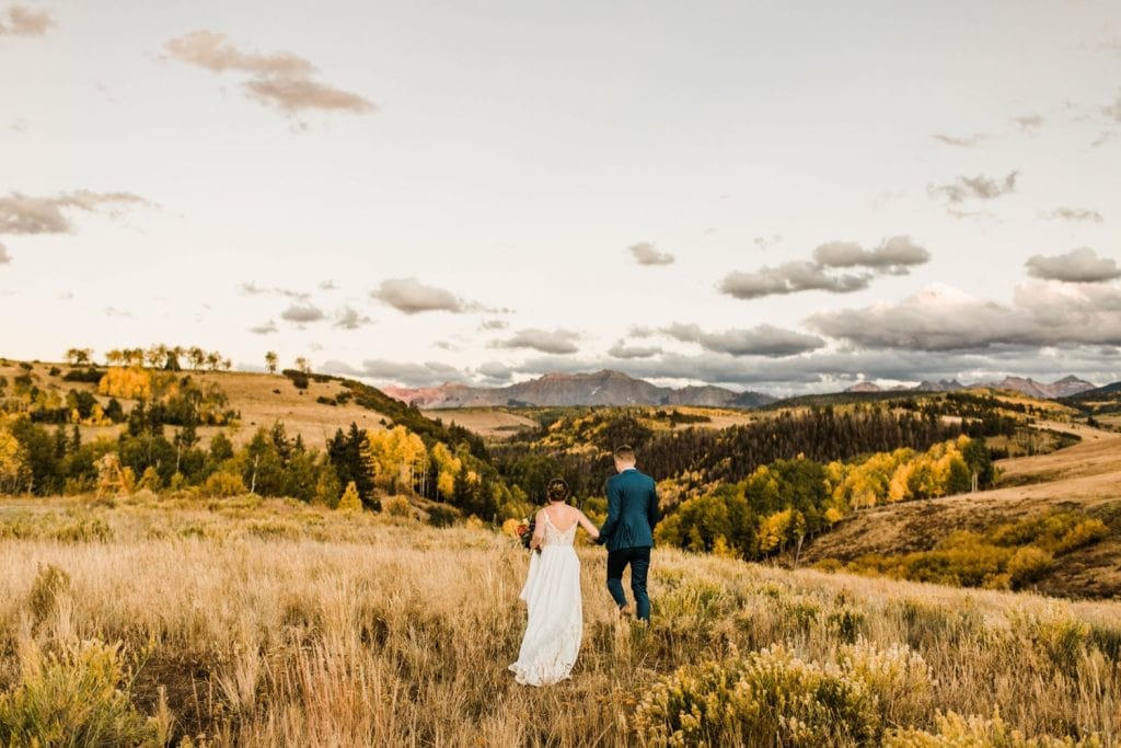 married couple walking through the mountains during their Telluride wedding sunset photos | photo taken by Telluride wedding photographers