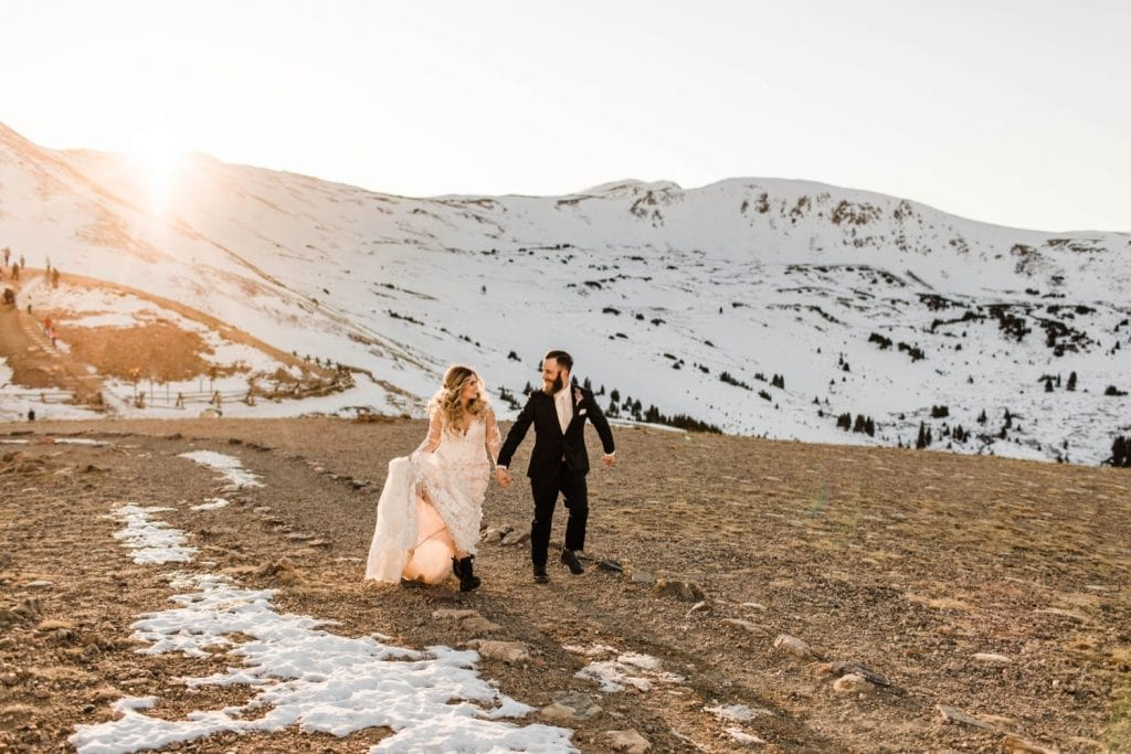 newly married couple running through the Rocky Mountains at sunset after their Sapphire Point Overlook wedding