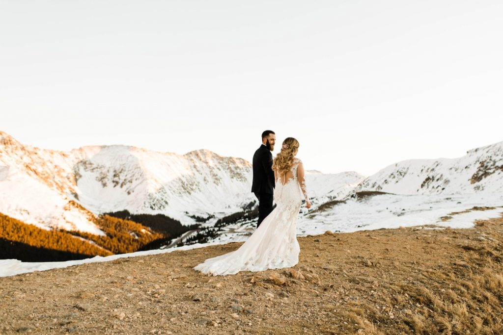 newly married couple walking on a hiking trail through the Rocky Mountains at sunset after their Sapphire Point Overlook wedding