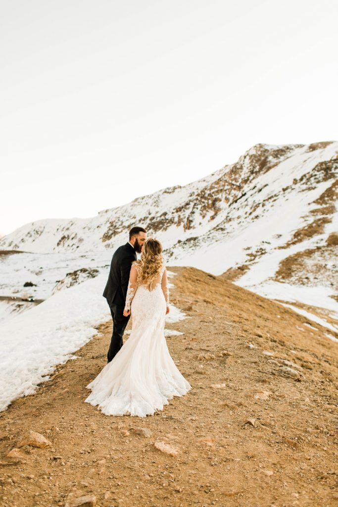newly married couple kissing on a hiking trail through the Rocky Mountains at sunset after their Sapphire Point Overlook wedding