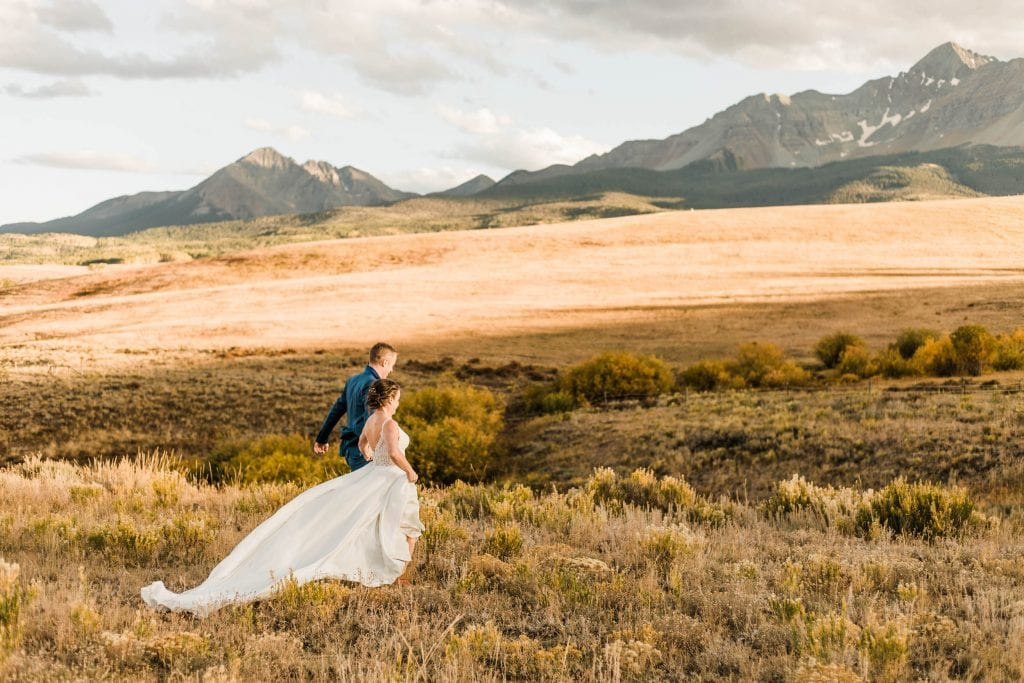 married couple running through the mountains during their Telluride wedding sunset photos | photo taken by Telluride wedding photographers