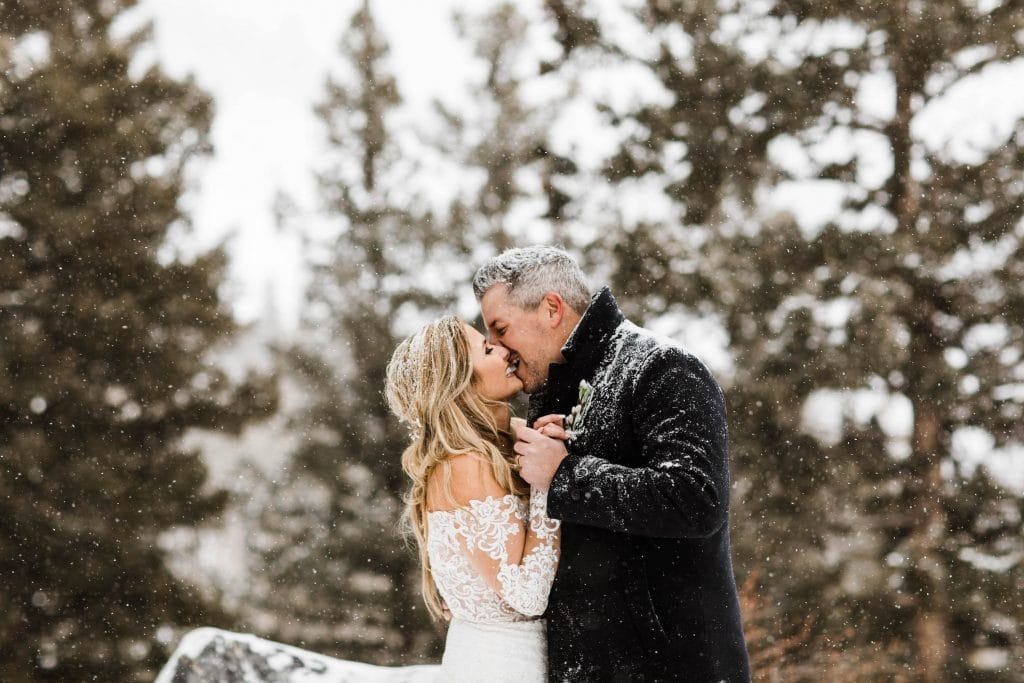 elopement definition example of couple sharing their first kiss after eloping in the snow