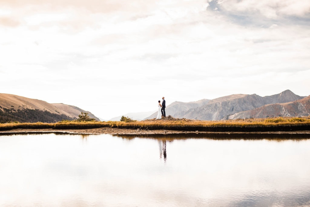 Colorado eloping couple enjoying the sunrise in the alpine tundra by a lake