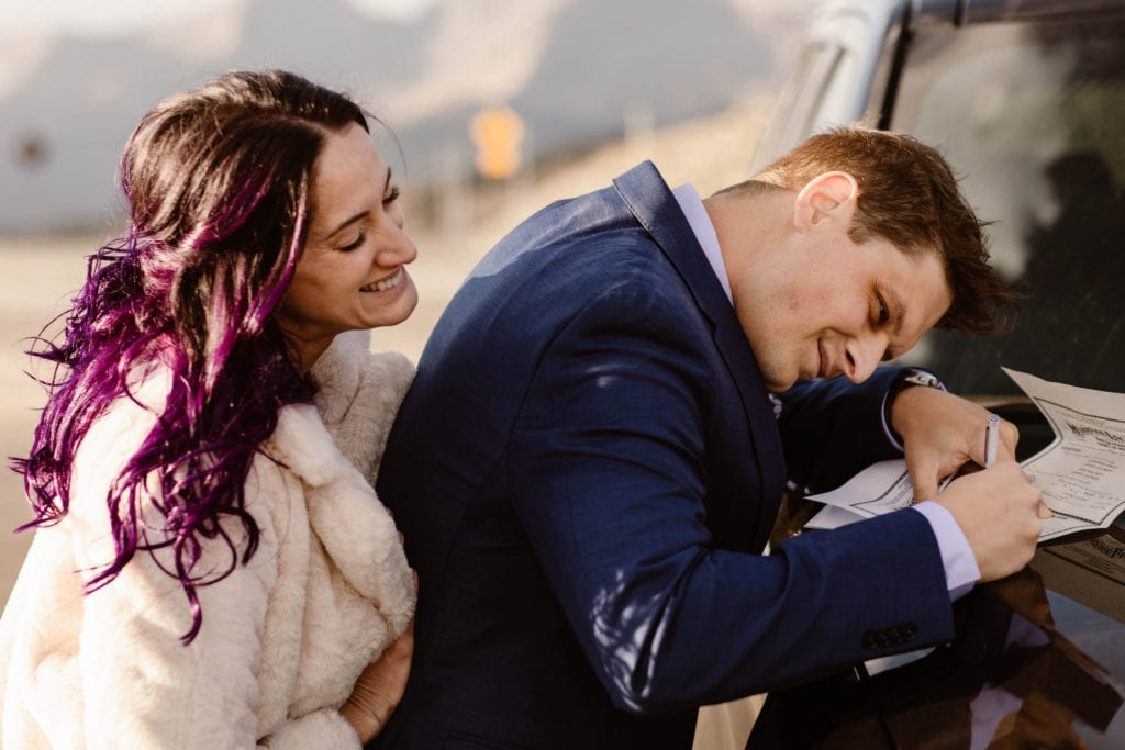 couple showing how to elope in Colorado by signing their Colorado marriage license