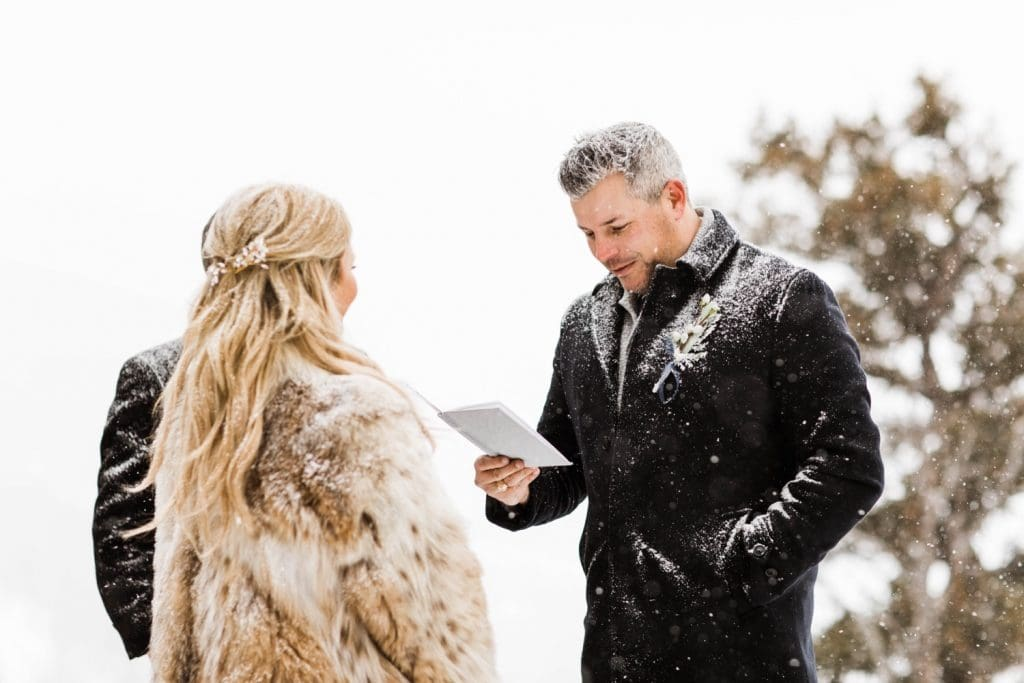eloping couple reading their vows to each other during their winter Sapphire Point elopement ceremony