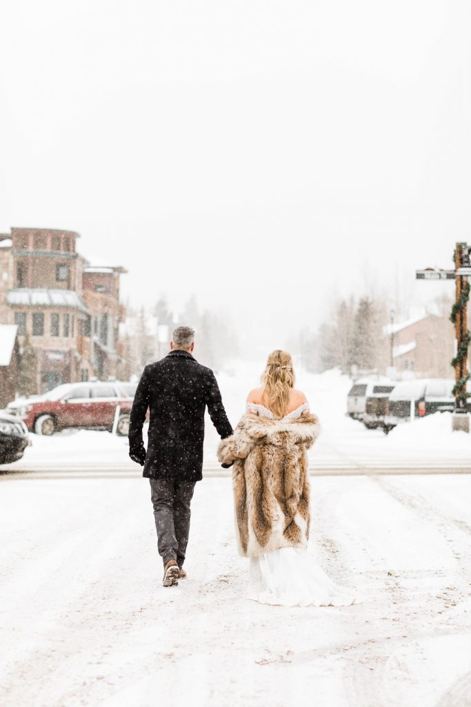 eloping couple walking through downtown Frisco Colorado after they eloped at Sapphire Point Overlook