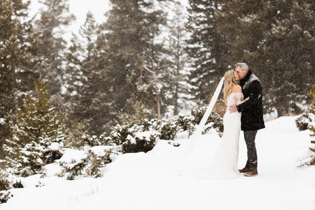eloping couple kissing in the snowy mountains at Sapphire Point Overlook after their elopement