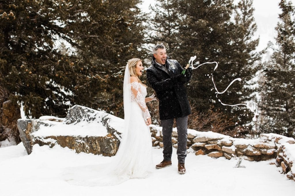 eloping couple popping champagne for their snowy winter Sapphire Point elopement