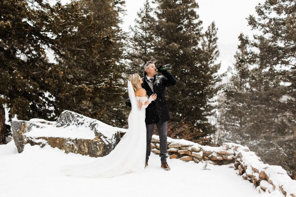 groom drinking champagne to celebrate his winter Sapphire Point elopement in the snow