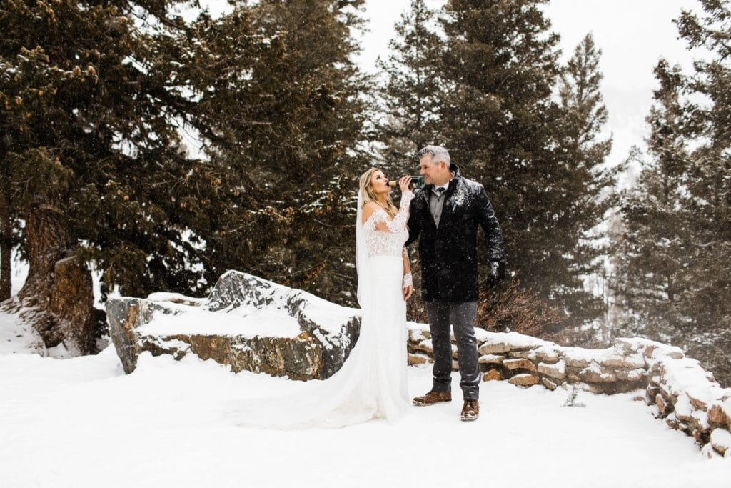 bride drinking champagne to celebrate her winter Sapphire Point elopement in the snow