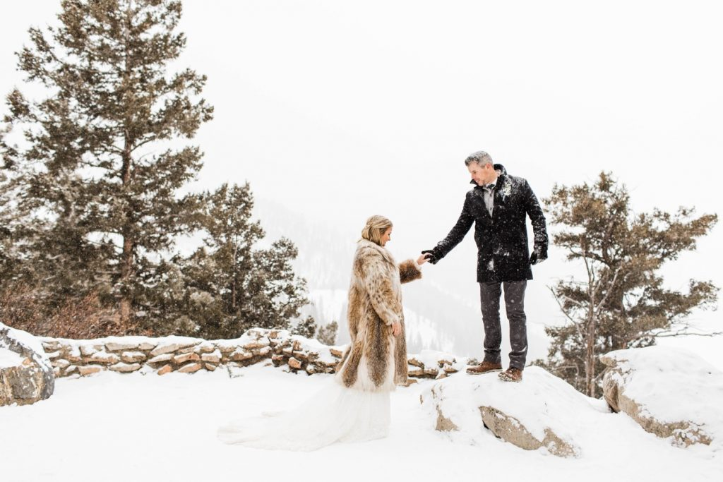 eloping couple walking in the snow at their Sapphire Point elopement