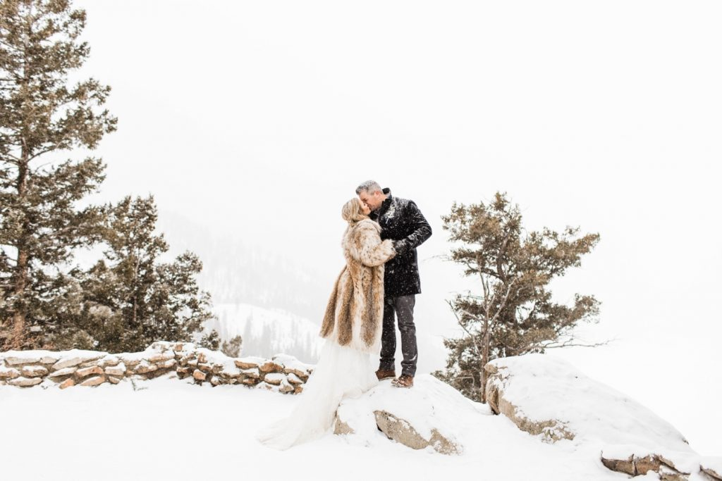 eloping couple kissing in the snow at their Sapphire Point elopement