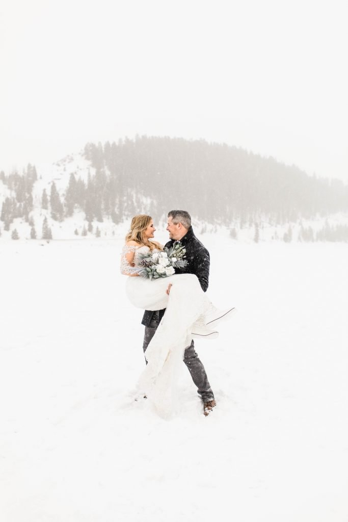 groom lifting and spinning bride around in celebration after their Sapphire Point elopement in the winter