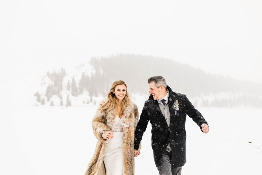 eloping couple running through the snow after their Sapphire Point elopement ceremony