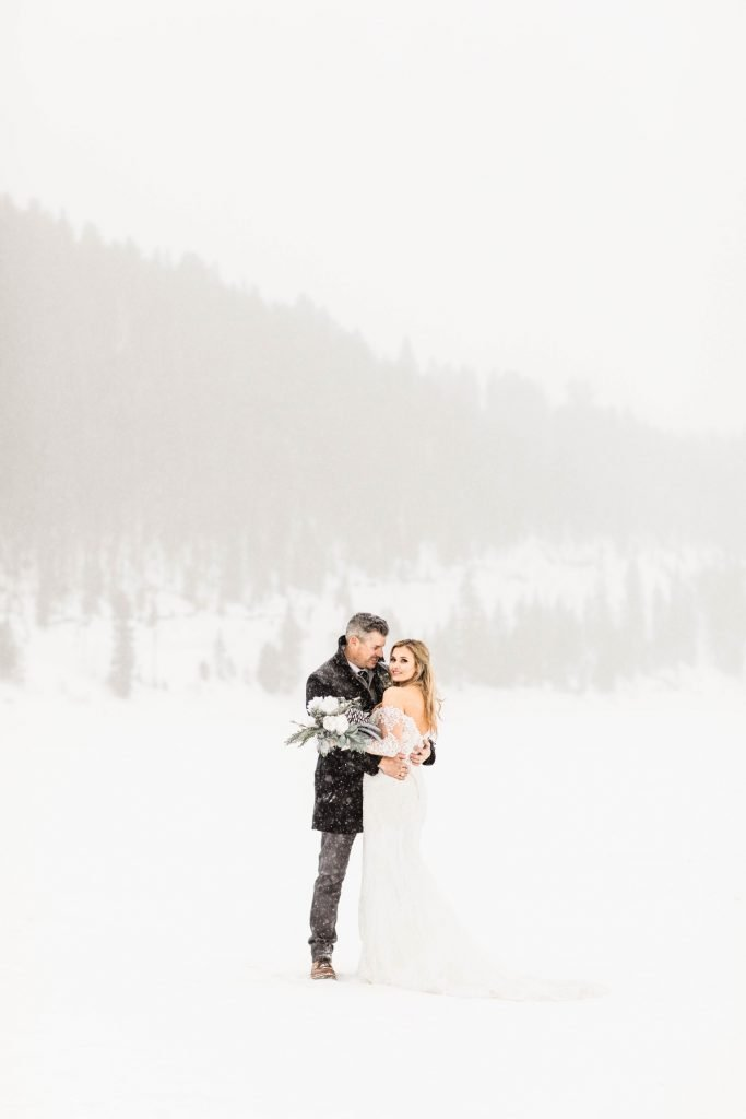 couple standing together in the snowy mountains after they eloped at Sapphire Point Overlook