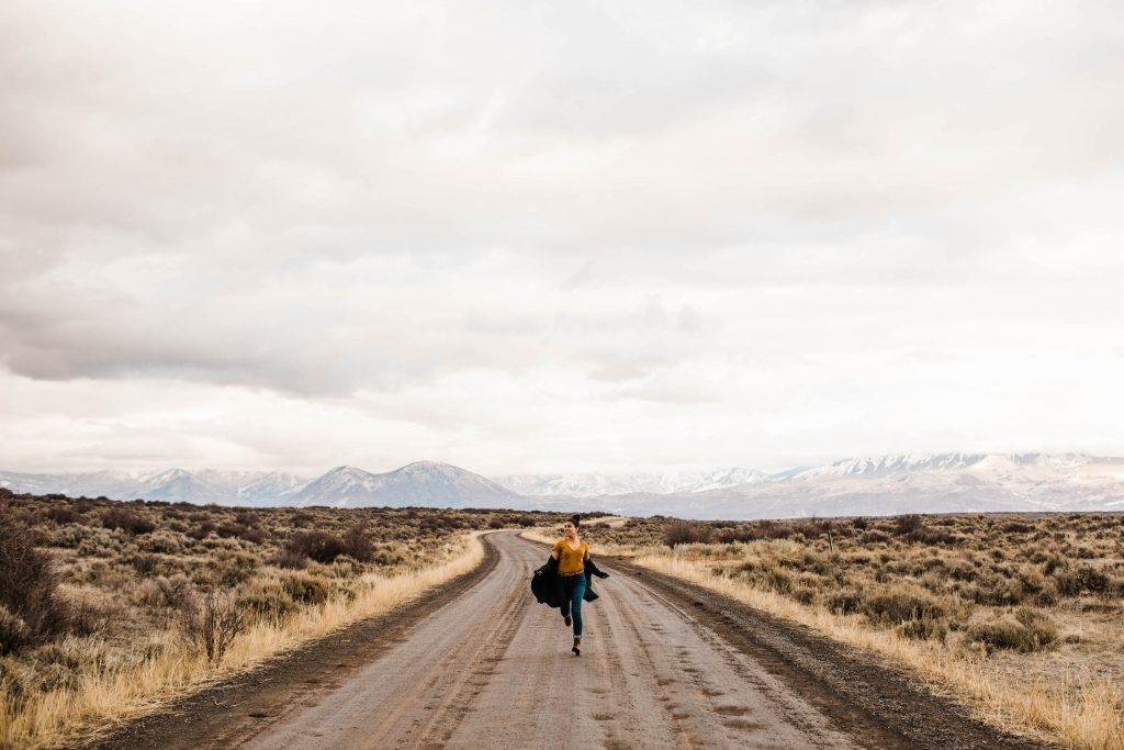 mountain elopement photographer running down a dirt road in the Rockies