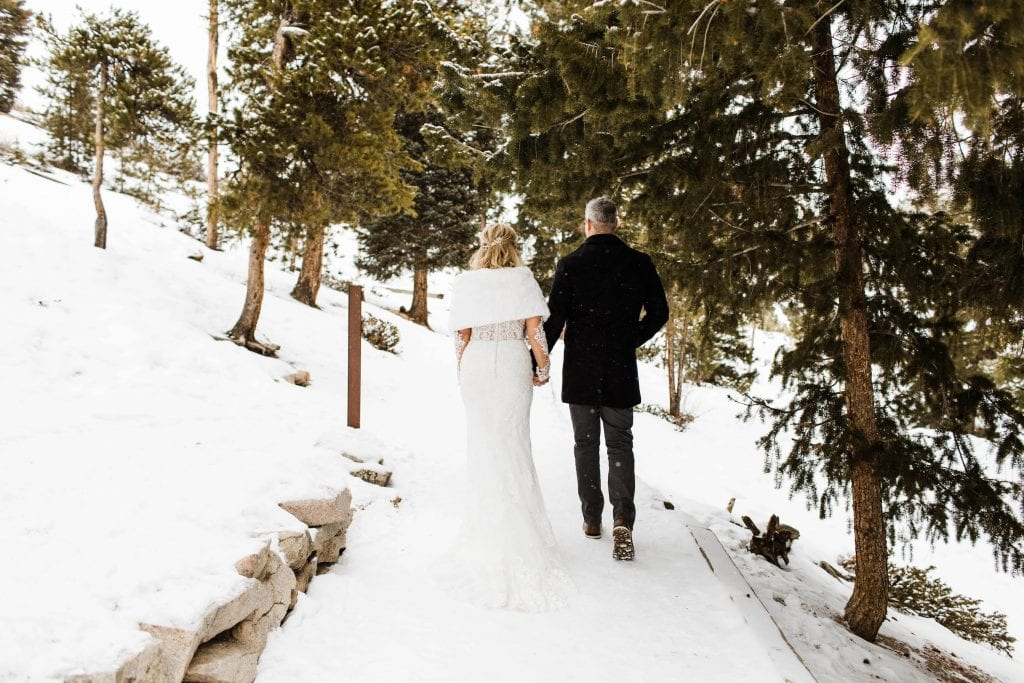 couple eloping in the mountains on a hiking trail in the snow