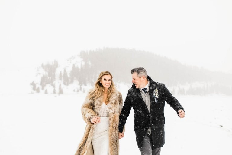 couple running in the snow during their Colorado elopement photographed by adventure wedding photographers
