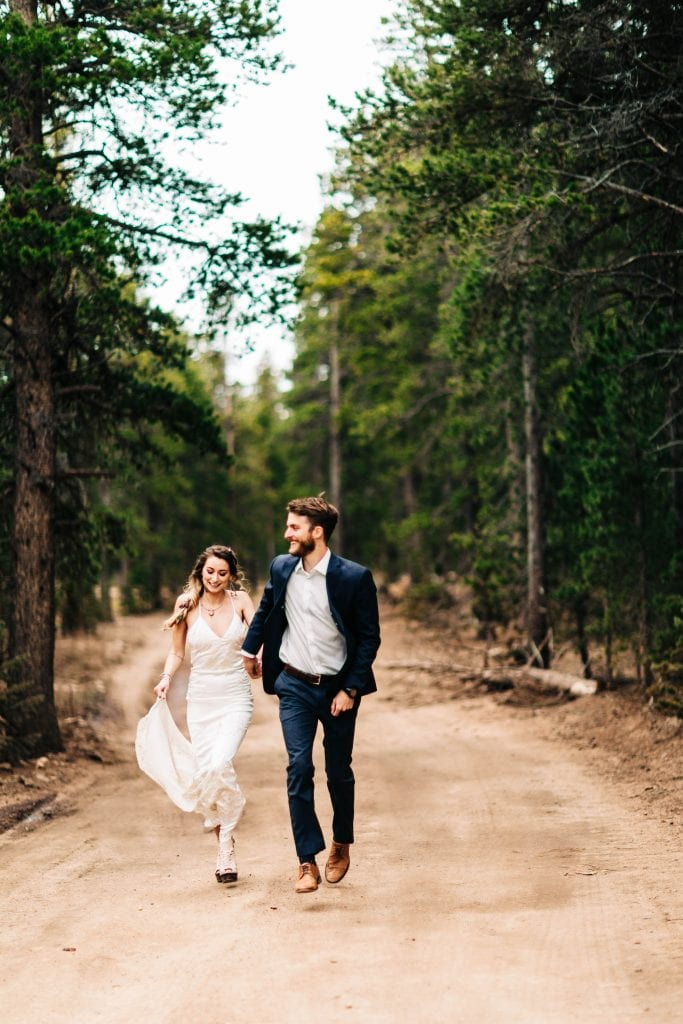 camper van Colorado elopement photo of couple running on a dirt road during their adventure wedding