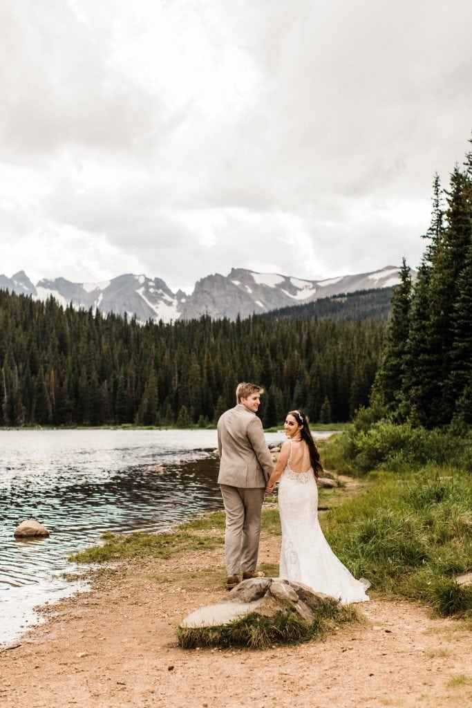 couple hiking around a lake after their mountain wedding in Colorado