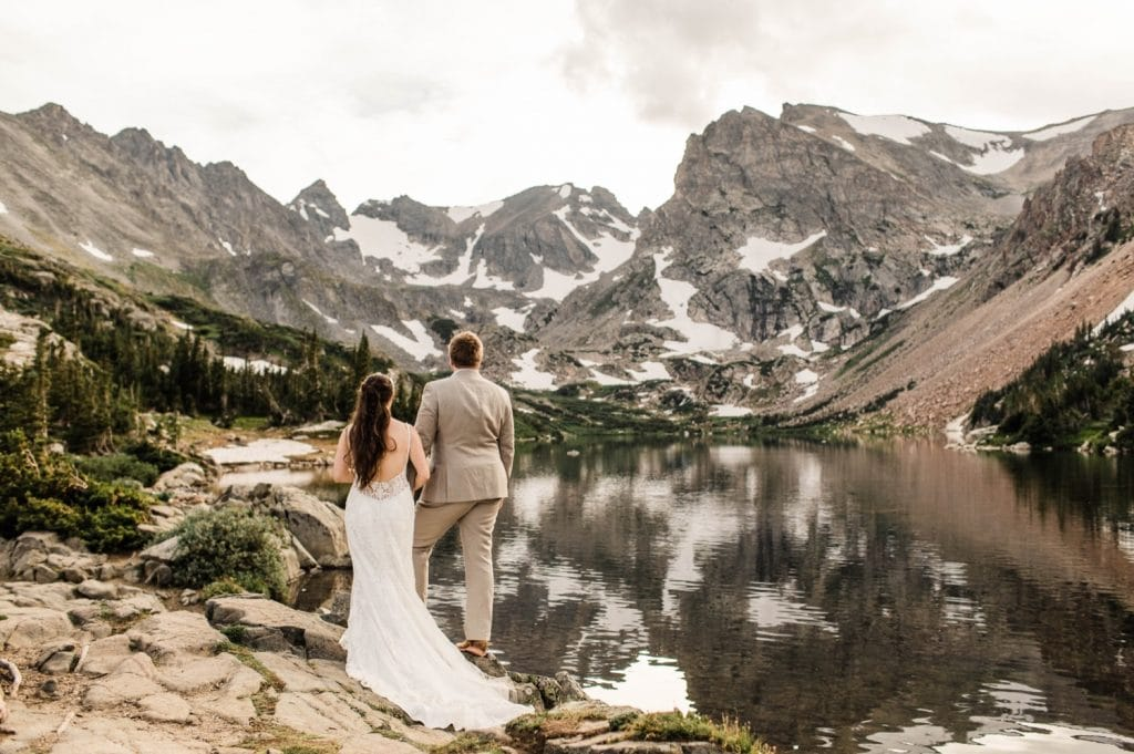 married couple looking out at the mountains on a hiking trail in Colorado