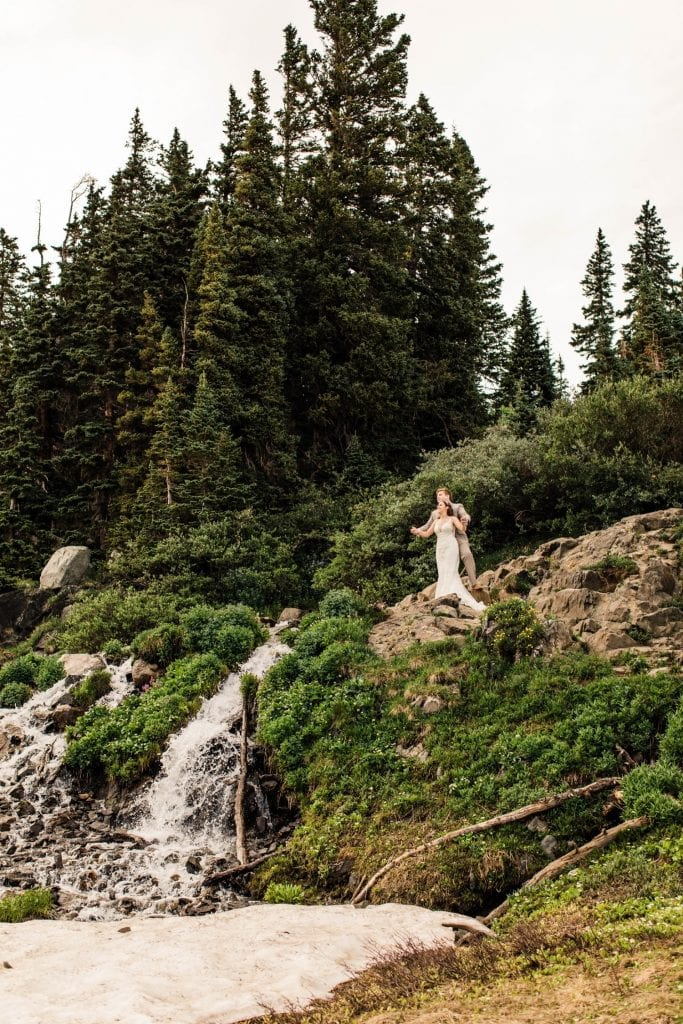 mountain wedding in Colorado where a couple hikes past a waterfall in the high country