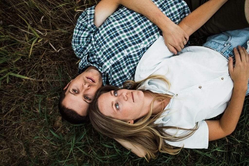 couple laying in the grass during their adventurous Colorado engagement photo session