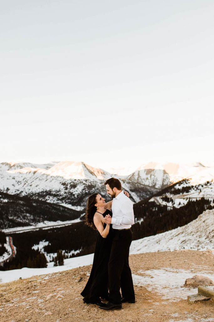 Colorado engagement photos of a couple dancing on a snow covered mountaintop