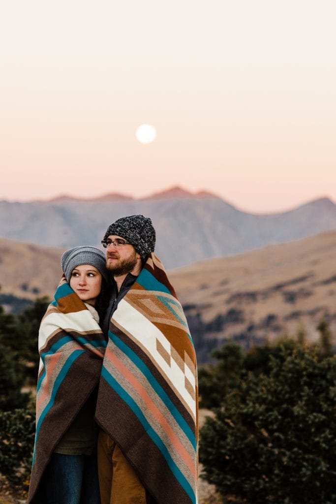 couple standing under a full moon while having their photo taken by a Colorado engagement photographer