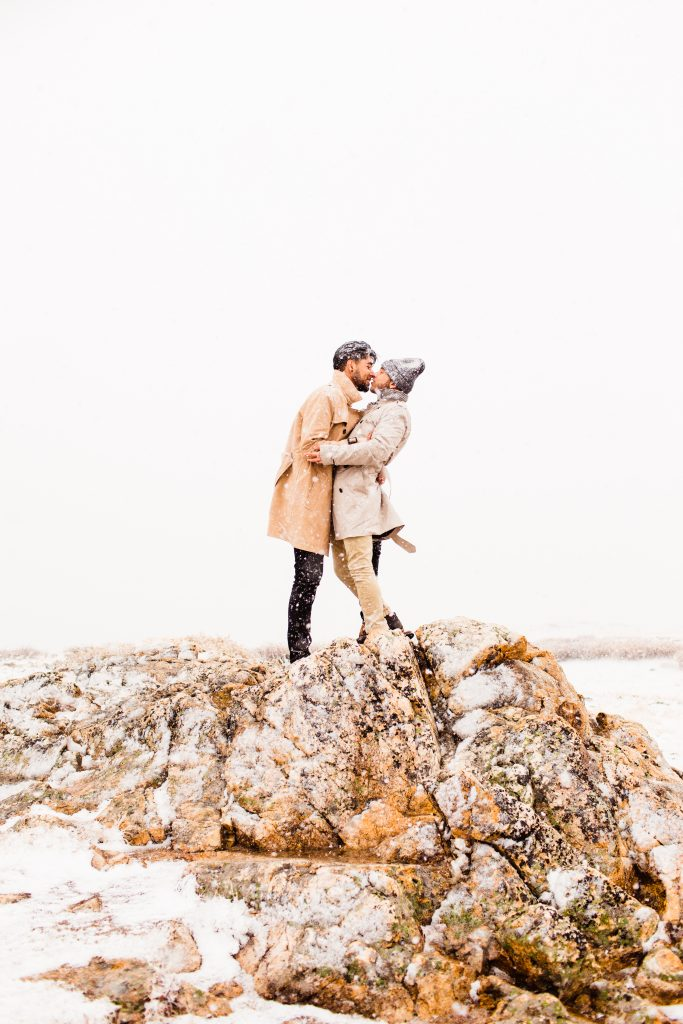 engaged couple kissing in the middle of a snowstorm