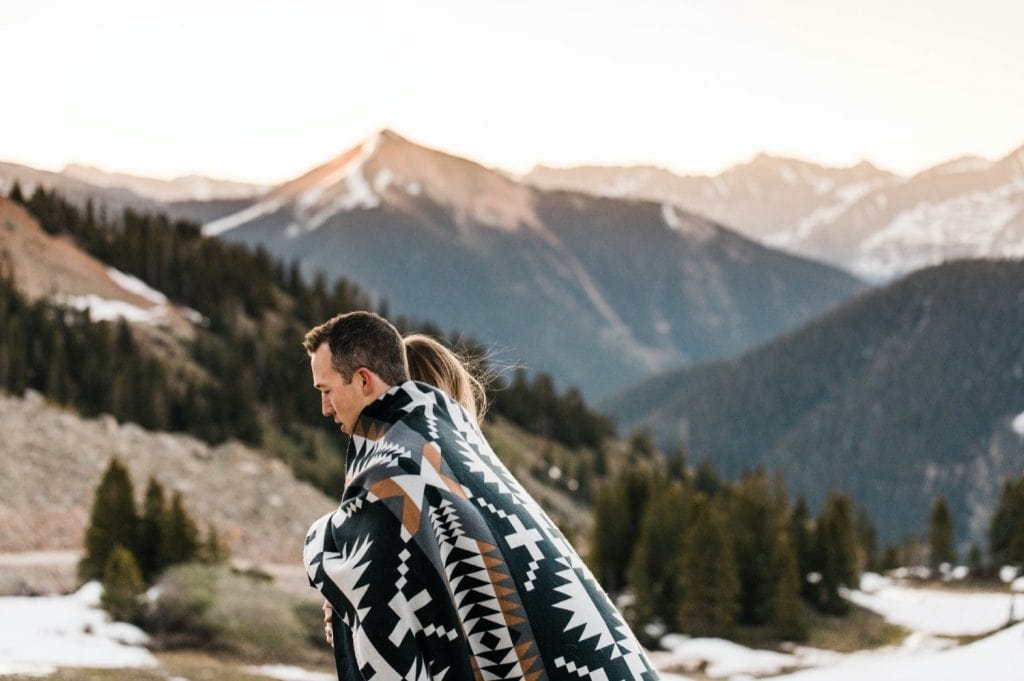 Telluride elopement couple wrapped up in a blanket while watching the sun rise in the mountains