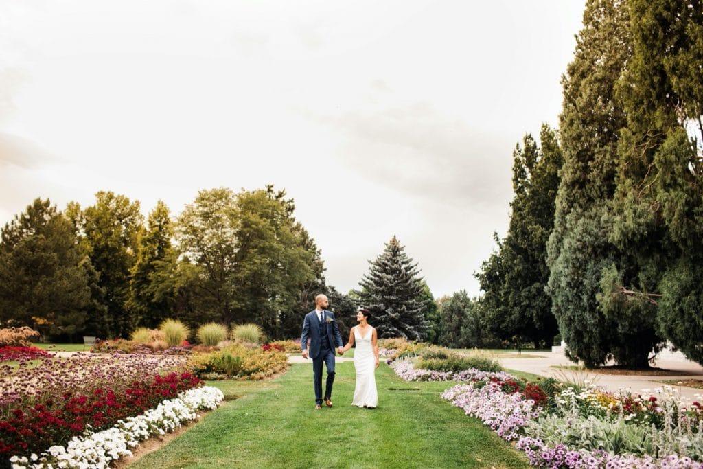 couple walking through a garden before their Denver Botanic Gardens wedding