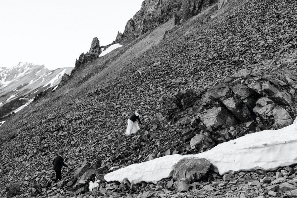 bride and groom scrambling up the side of a mountain to say their vows during their elopement in Telluride