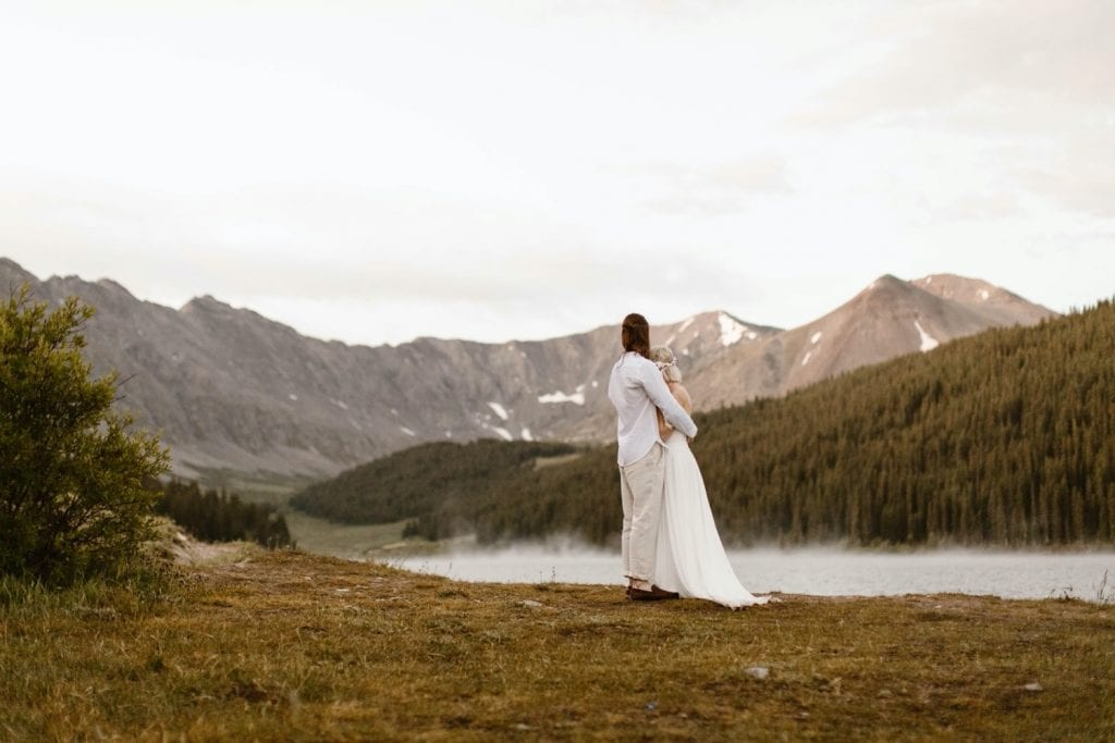 couple admiring a steaming alpine lake before they begin their lake wedding ceremony at sunrise