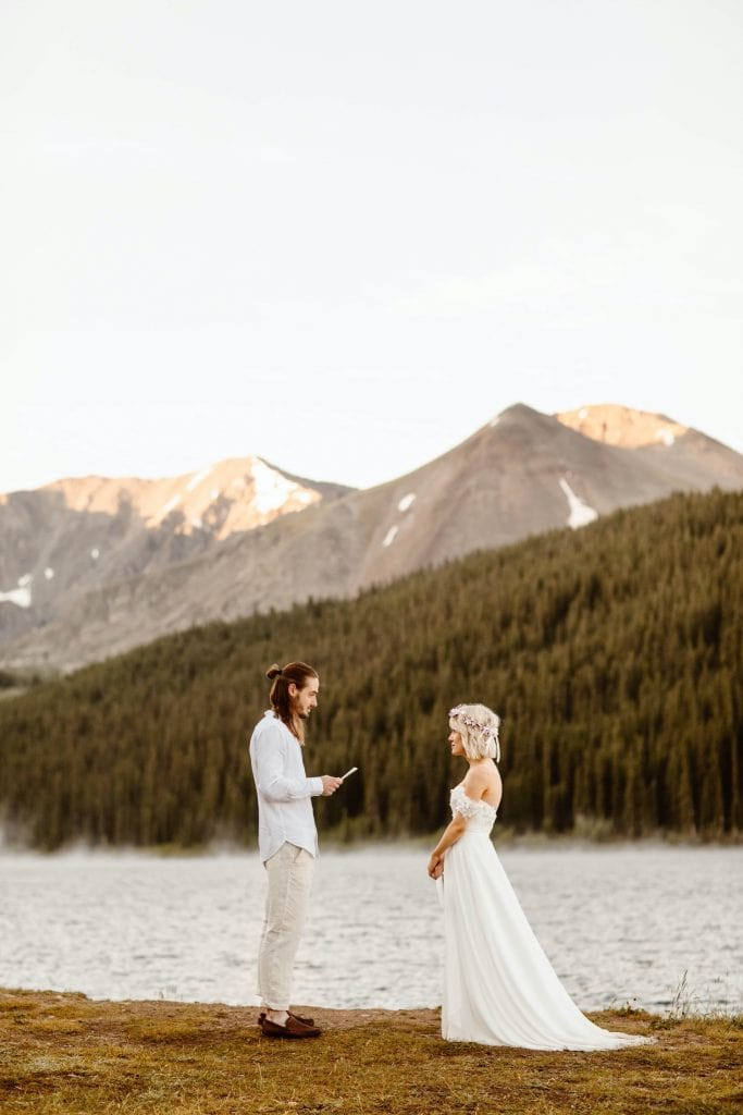 eloping couple reading their vows during their lake wedding ceremony in Colorado
