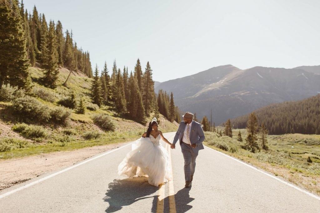 couple running on a mountain pass during their Aspen elopement