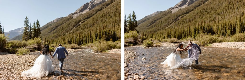 couple wading through a creek in their wedding attire after they eloped in Aspen Colorado
