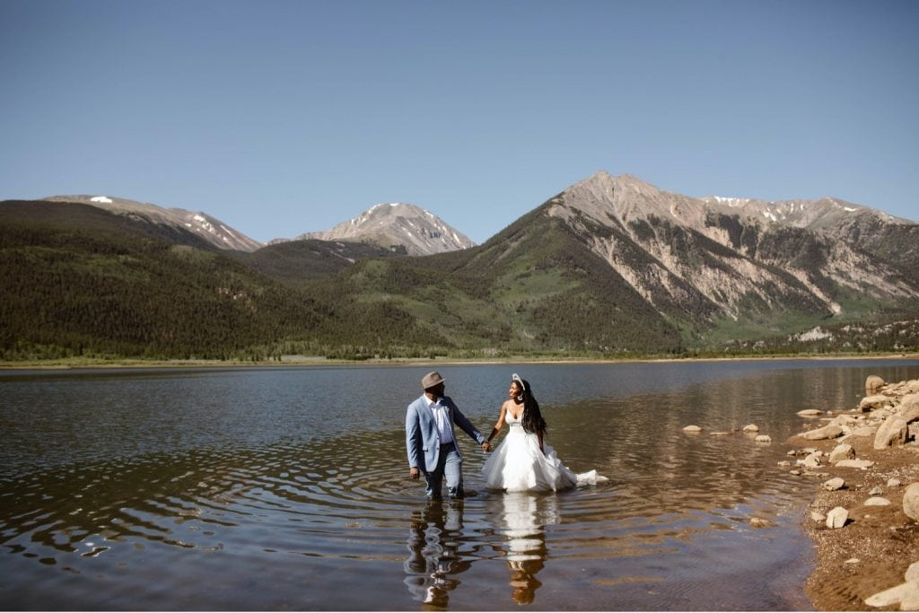 couple getting into a lake in their wedding attire after they eloped in Aspen Colorado