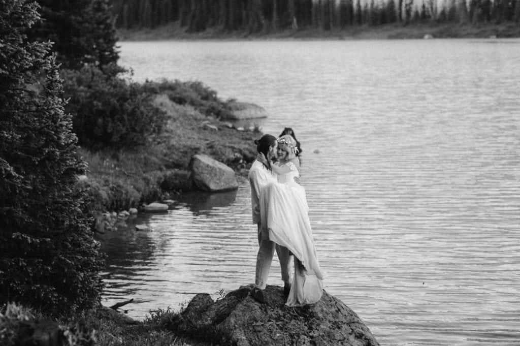 eloping couple adventuring on a trail in the mountains during their lake wedding in Colorado