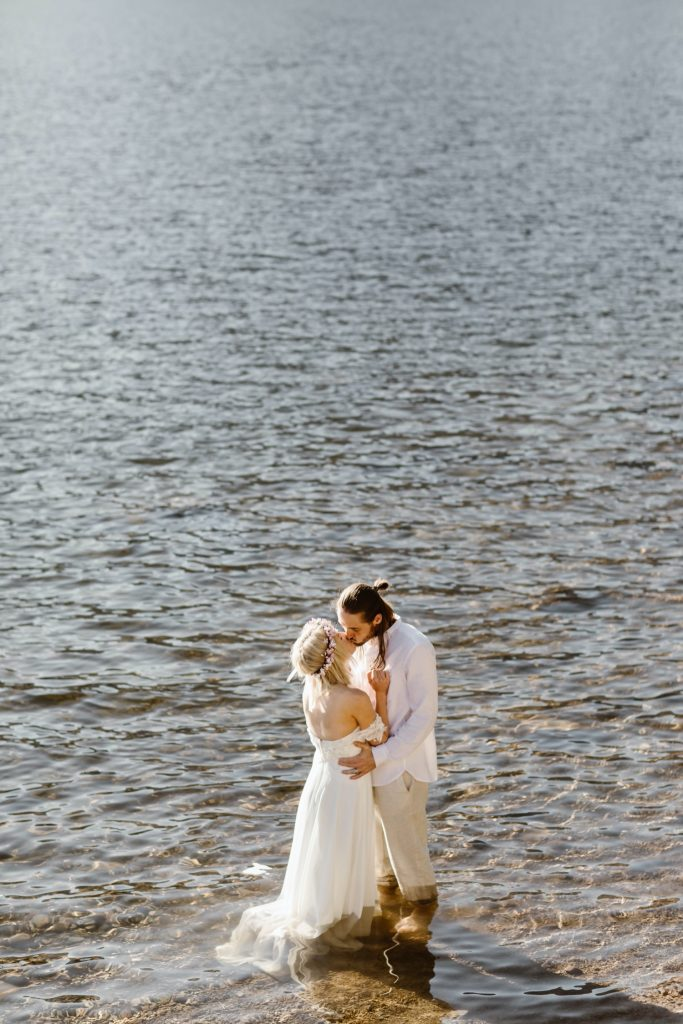 couple wading into the water after their lake wedding ceremony