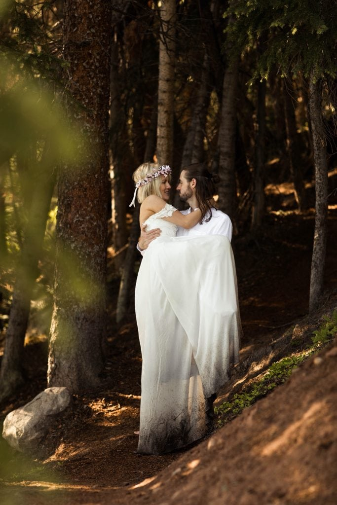 groom lifting the bride for a kiss in the forest after their elopement wedding