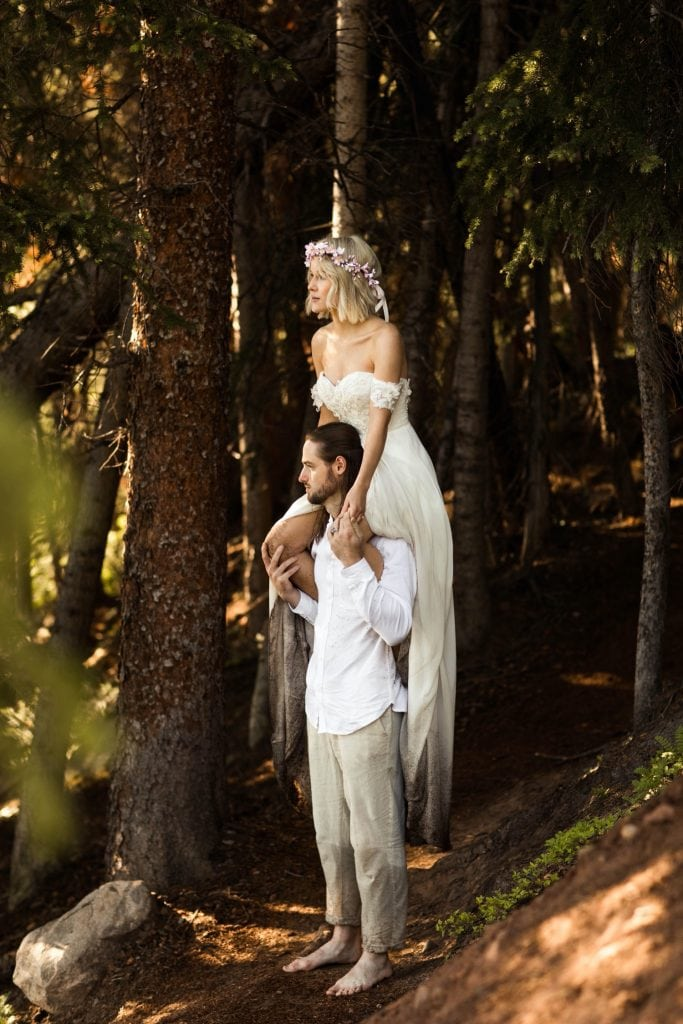 bride sitting on groom's shoulder while hiking in the forest after their elopement ceremony