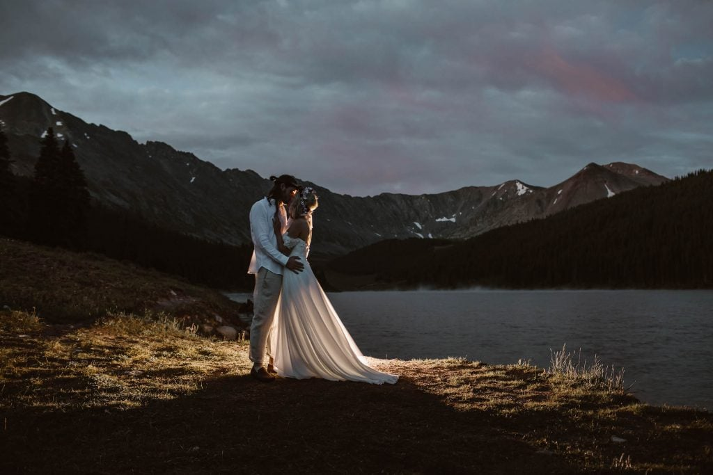 bride and groom kissing at blue hour in the mountains before their adventure wedding ceremony documented by Colorado elopement photographers