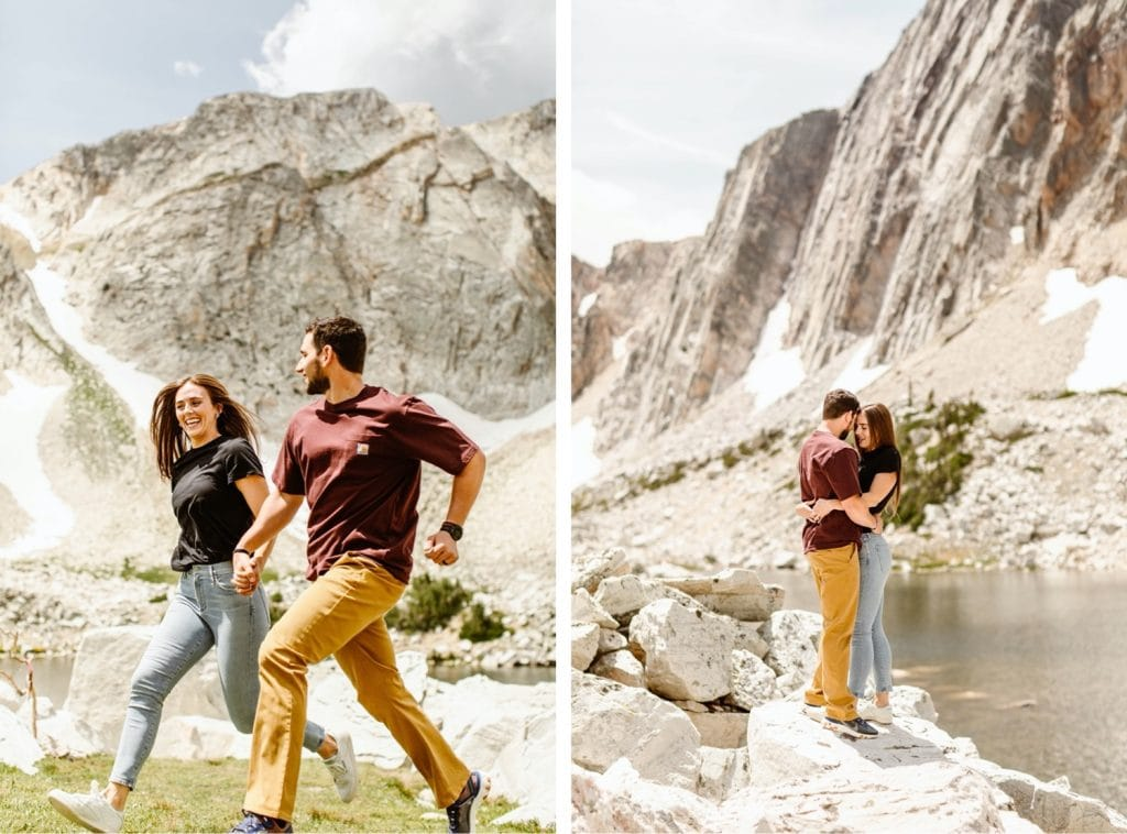 couple running through a field during their mountain engagement photos in Wyoming