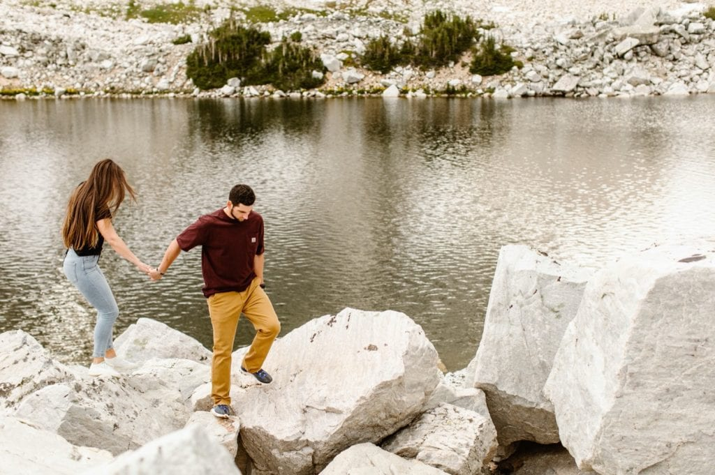 couple hiking through a boulder field while having their mountain engagement photos taken in Wyoming